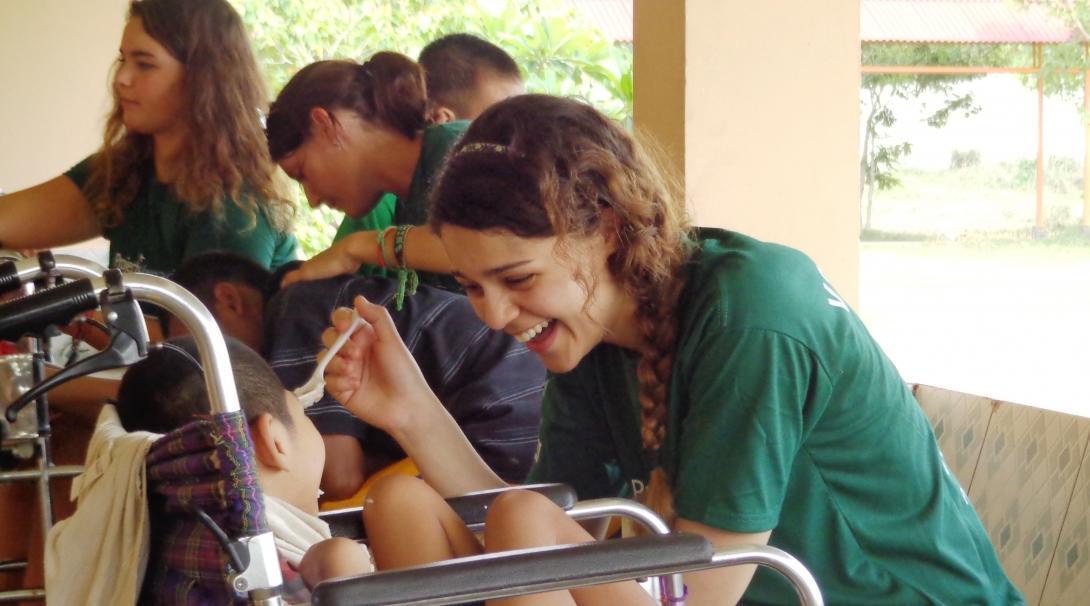 Interna ayudando a un niño a comer como parte de sus prácticas de terapia ocupacional en Camboya.